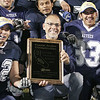 Farmersville High School Principal Ernie Flores show off the CIF Central Section Division VI championship plaque as Daniel Salud (72) and Isaiah Hernandez (33) celebrate.