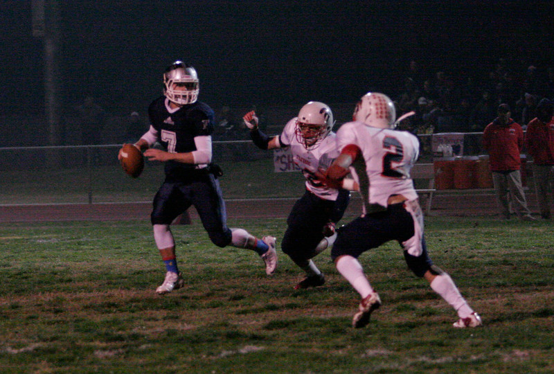 Farmersville Aztec quarterback Sam Metcalf (7) tries to roll away from the Strathmore rush during the Central Section Division VI final. Farmersville defeated Strathmore 47-35 to win the championship.
