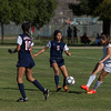 Strathmore Spartan forward Samantha Oliveira (23) kicks a pass between Maranatha Minutemen defenders Andrea Gamez (5) and Alexis Phillips (10) during the 2015 CIF Southern California Division IV Soccer Championship final.