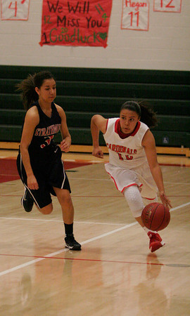 Lindsay's Christina Castro (10) dribbles around Strathmore's Kandyce Gurrola (3) during the Cardinal's 81-38 victory in Friday.