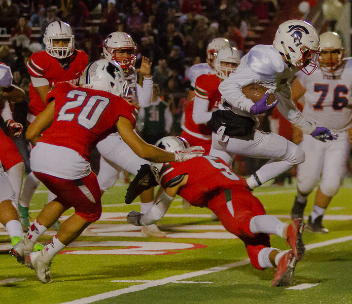 Strathmore Spartan RB Cristan Rodriguez (3) tries to hurdle Lindsay Cardinal CB Mario Diaz (5) during their annual rivalry game. The Cardinal would hold on for a 10-7 victory in the Bell Game.