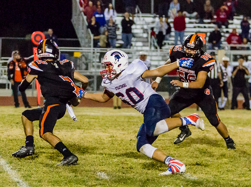 Brenardo Navarro (50) a LB for the Strathmore Spartans grabs a handful of the jersey of Woodlake Tiger QB Damian Hernandez. Hernandez was under pressure all night in the Tigers 26-22 loss to the Spartans.