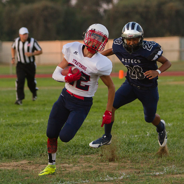 Strathmore Spartan RB Alonso Acevedo  turns the corner as Farmersville Aztec defender Noah Vasquez (28) pursues. Acevedo carried  3 times for  90 yards  and 1 touchdown in the Spartan's 42-6 non-league victory.