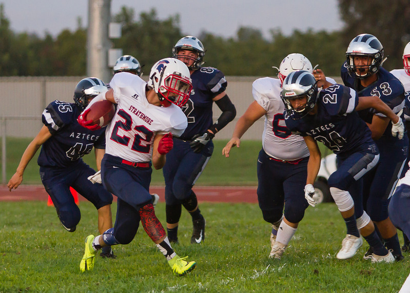 Strathmore Spartan RB Alonso Acevedo (22) attempts to escape a host of Farmersville Aztec defenders during their season opener at  Farmersville. The Spartans rolled to a 42-6 victory.