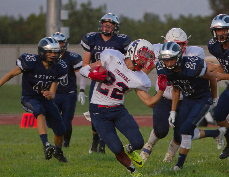 Strathmore Spartan RB Alonso Acevedo (22)  attempts to elude Farmersville defenders Jacob Garcia (45) and Gabriel Silva (24) in the season opener for both teams. The Spartans rolled to  42-6 win.
