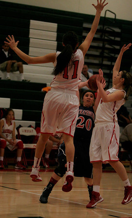 Linsday's Megan Salinas (11) and Ashley Baker (4) sky to block Strathmore's Shelby Vanasen's shot during their February 26th playoff game.