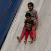 Two participants in The Spirit and Bride Kingdom Celebration enjoy the Hippo Slide, the world's largest inflateable slide, at the McDermont Field House on Saturday, June 14, 2014.