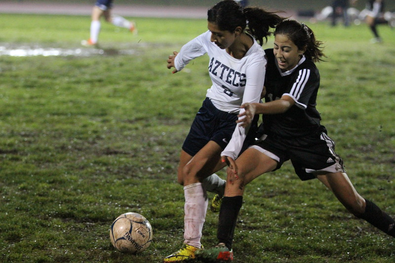 Aztec middle fielder Janette Rodriguez and Tiger middle fielder Briana Guerra scramble for the ball during Farmersville's 3-2 victory over Woodlake on Tuesday, December 2nd.