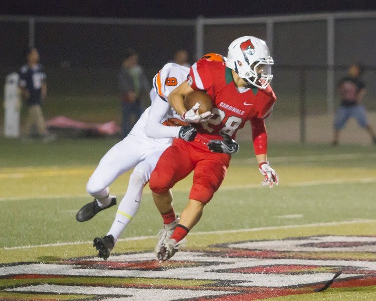 Lindsay RB Ethan Duran (28) rushes the football in the Cardinal's homecoming contest against the Woodlake Tigers as Tiger DB Tell Blanke (8) attempts to bring him down. Lindsay won the hard fought ESL contest by a 14-12 score.