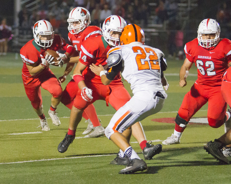 Lindsay RB Ethan Duran (28) takes the hand off from Cardinal QB Ethan Natera (1) as Javier Avalos (44) puts a block on Woodlake defender Autistic Austin (22). Lindsay prevailed in this ESL contest by a 14-12 score.