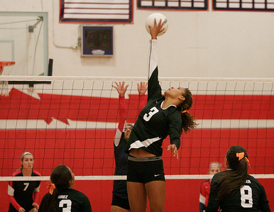 Woodlake Tiger Kinna Cunningham (3) goes high for the volleyball against Strathmore's Josie Lopez during Thurdsay's match. Woodlake won the match 3-1.