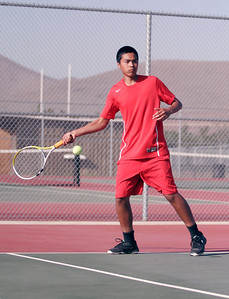 Lindsay High School tennis player Arturo Corona returns a serve to his Woodlake opponent during their Thurdsay, March 20th match.