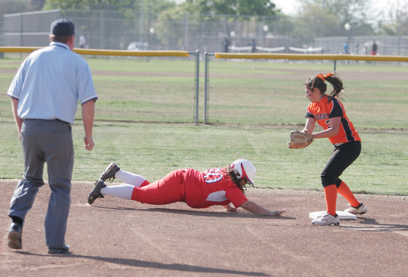 Lindsay Cardinal Emily Rojas dive back to second base to avoid being picked off during Lindsay's game with Woodlake on Friday.