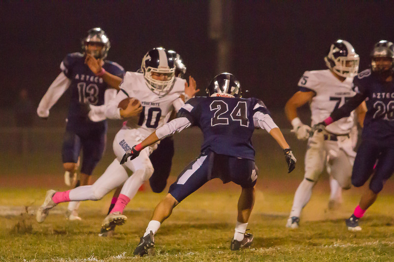 Farmersville Aztec Gabriel Silva (24) prepare to tackle Yosemite Badger Quarterback Tyson Manfied (10) during there battle on Friday night. Silva would finish with 8 tackles in this up and down contest. Farmersville fell short in a 35-33 battle.