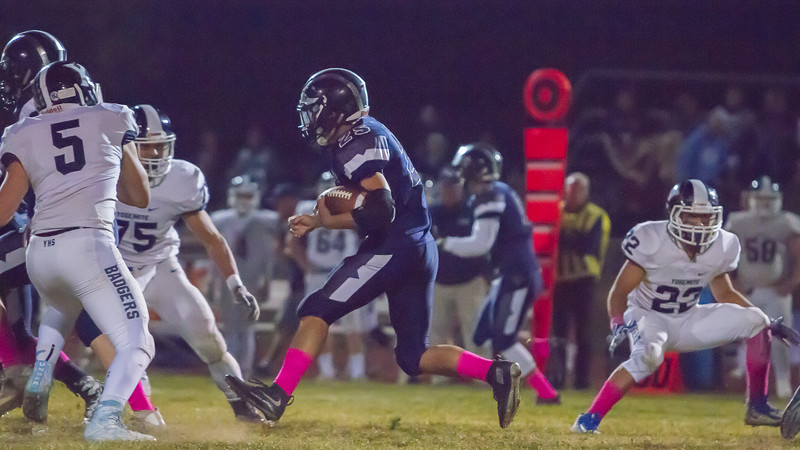 Aztec RB David Contreras (25)  rushes against the Yosemite Badger in Farmersville's non-league game. The Aztecs dropped a hard fought contest to an undefeated Badger team by a 35-33 score.