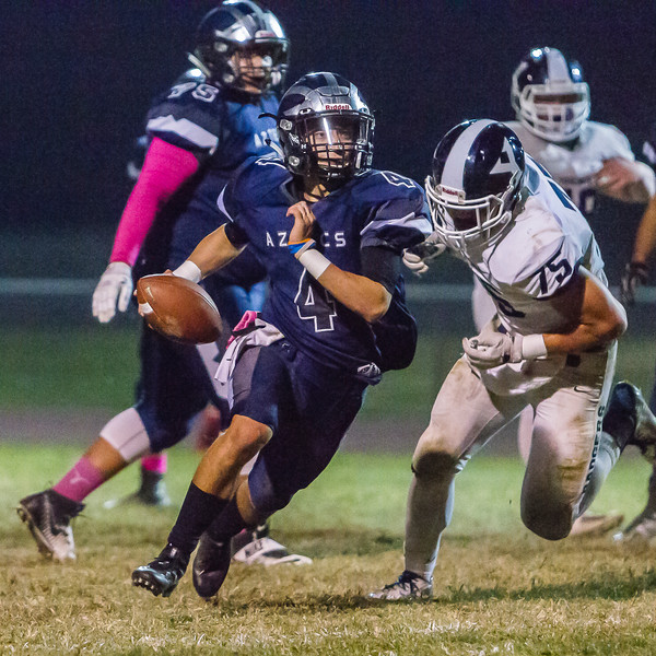 Farmersville  Aztec QB Victor Castrejon eludes a Yosemite Badger defender on the way to scoring one of his two touchdowns on the night. The Aztecs dropped a hard fought contest 35-33 to the undefeated Badgers.