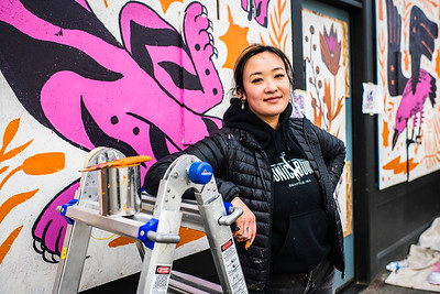 Stevie Shao paints a mural in the Ballard neighborhood in Seattle. Shao is one of five artists comissioned by the Ballard Alliance to paint murals on the plywood covering local businesses that closed due to the government mandated shelter in place order.