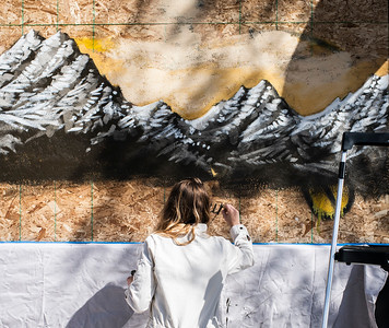 Laura Burkhart paints a mural on the plywood covering up September, a local retail store in the Ballard neighborhood in Seattle. Burkhart is one of several artists to painted over the weekend in an effort to give the neighborhood some life amidst the Coronavirus crisis.