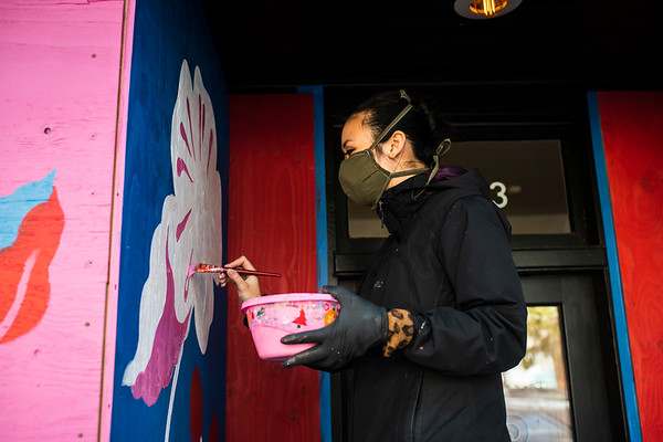 Tori Shao paints a mural in the Ballard neighborhood in Seattle. Shao is one of five artists comissioned by the Ballard Alliance to paint murals on the plywood covering local businesses that closed due to the government mandated shelter in place order.