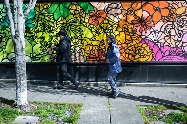 Seattle residents walk by one of several murals painted in the Ballard neighborhood. Artists took to the streets on Sunday to try and offset the impact of the Coronavirus crisis.