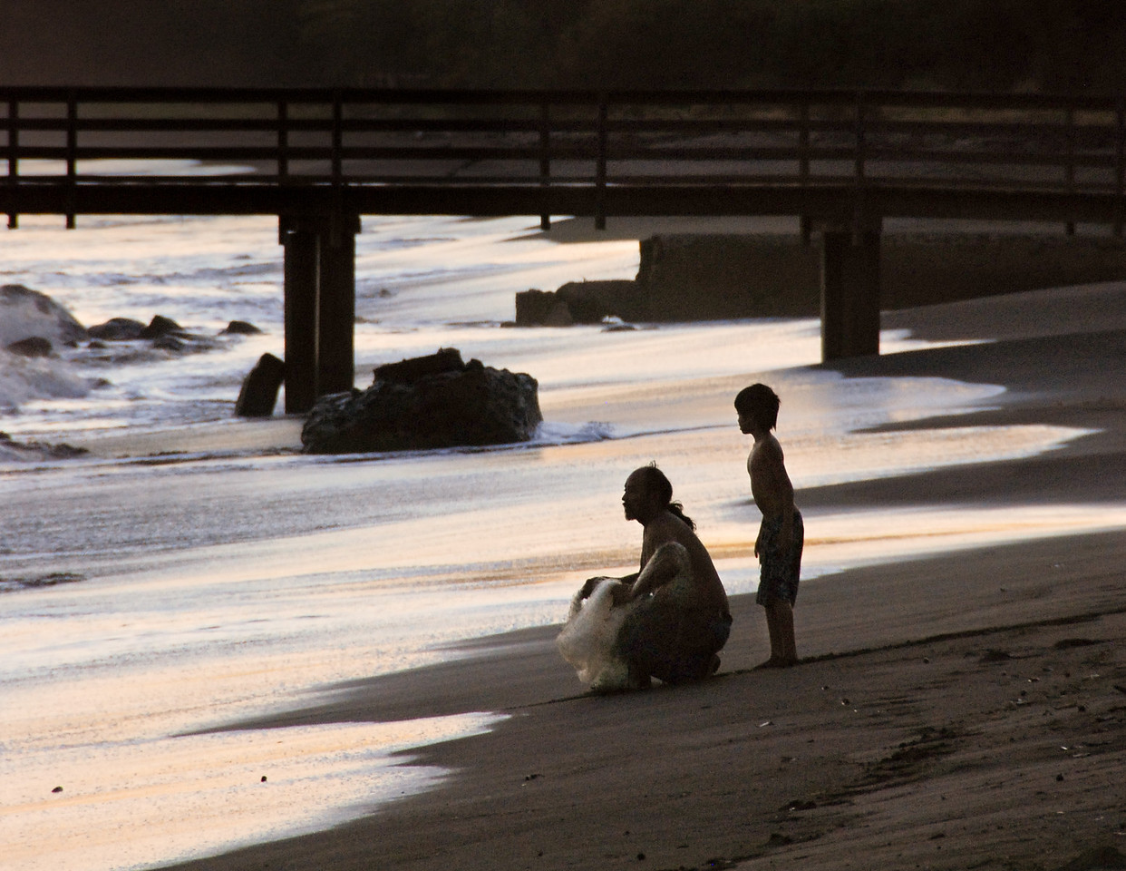 "June<br /> <br /> ""Learning from the Master""<br /> Fisherman and son<br /> Waimea Beach, Kauai, Hawaii"