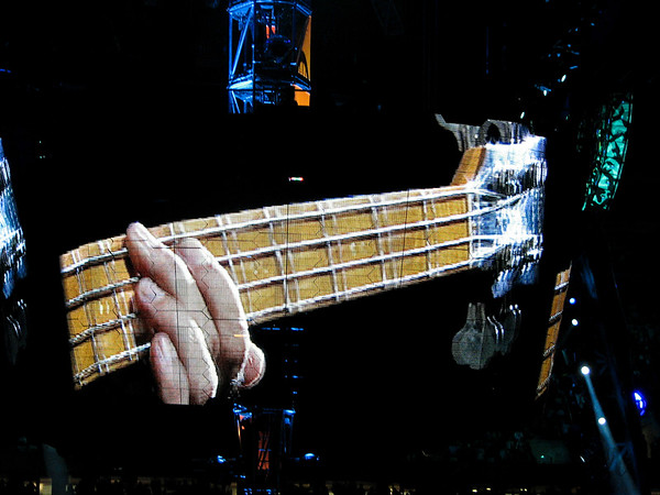 The Edge playing guitar. Taken from the wraparound screen during U2's 360 tour.