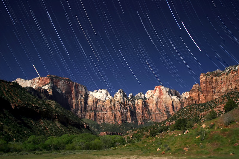 """""""Towers of the Virgin"""" <br><br> Zion National Park, UT<br><br> Zion National Park has some of the most amazing and rugged mountains and cliffs you will see anywhere.  This particular location is just behind the visitor center as you enter the park from the South.  A friend and I sat here for two hours shooting star trails with the full moon behind us to get this image. <br><br> Technical Details: Shot with Canon 10D and Canon 20mm lens at F2.8 and 30 seconds."""