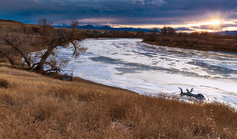 """""""Along the River"""" <br><br> Ulm, MT<br><br> I was born and raised in a little town in Montana named Great Falls.  As a Texan now I try as often as I can to get back to Montana and visit my family.  I also love to experience and photograph the Montana Scenery. <br><br> I came upon this scene as I explored around Great Falls one evening.  I loved the composition of the river flowing towards the mountains, all of it highlighted by the setting sun. <br><b> Technical Details: Shot with Canon 6D and Canon 24-105L lens at F16 and 1 second. <br><br><br></b><center><a><img src=""""/photos/604338366_ecXJp-M.gif""""></a></center>"""