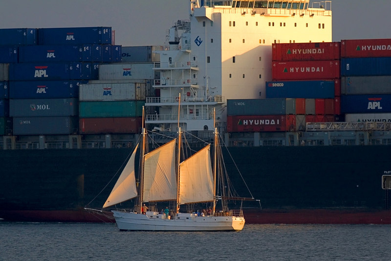 The tide and the sunset were at the same time, so big and little, the container ship and the sailboat, started their journeys next to each other.