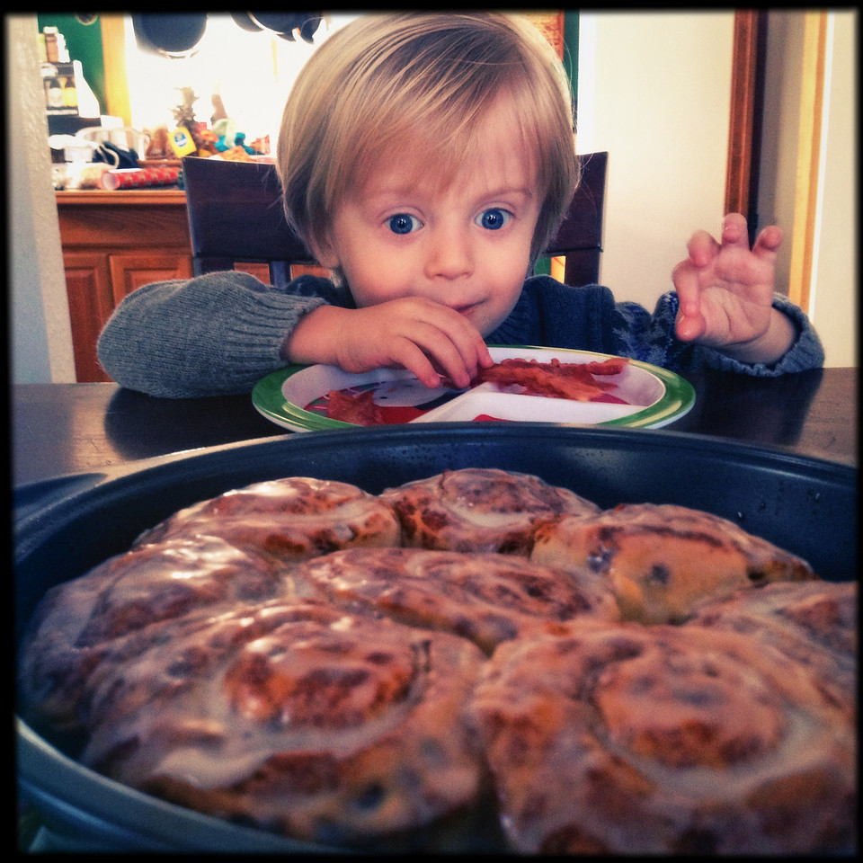 My son looks with wide-eyed joy at a pan of cinnamon rolls on Christmas morning.