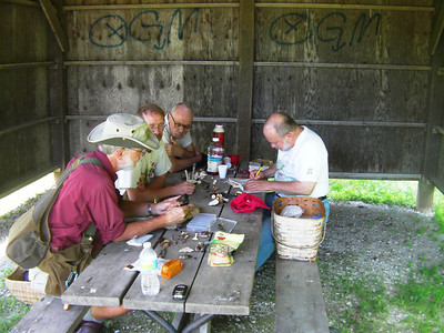 Gathered around the table, Roger, Glen Damian and Dean check out the finds.