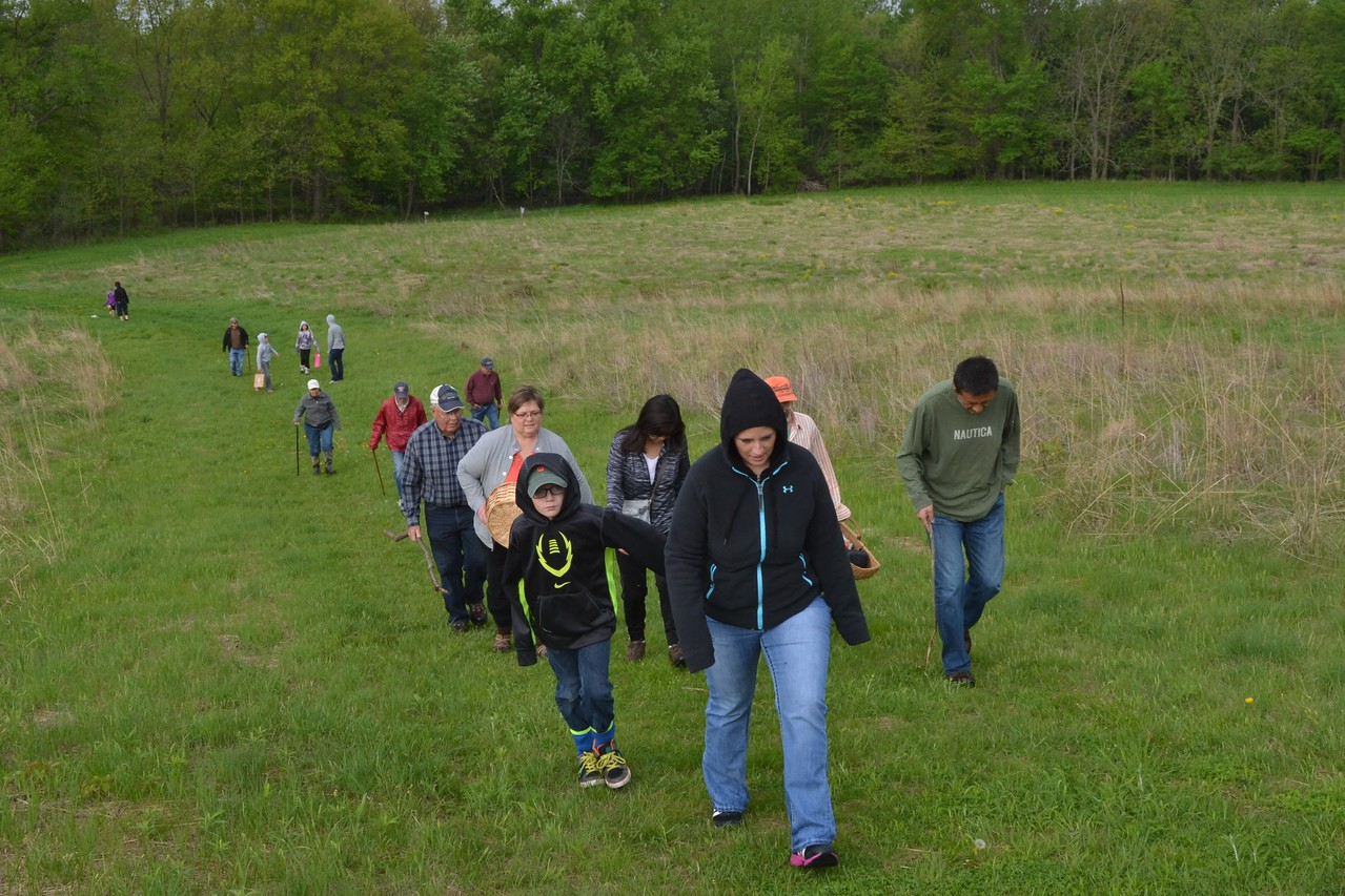 The group heads up the hill to the woods