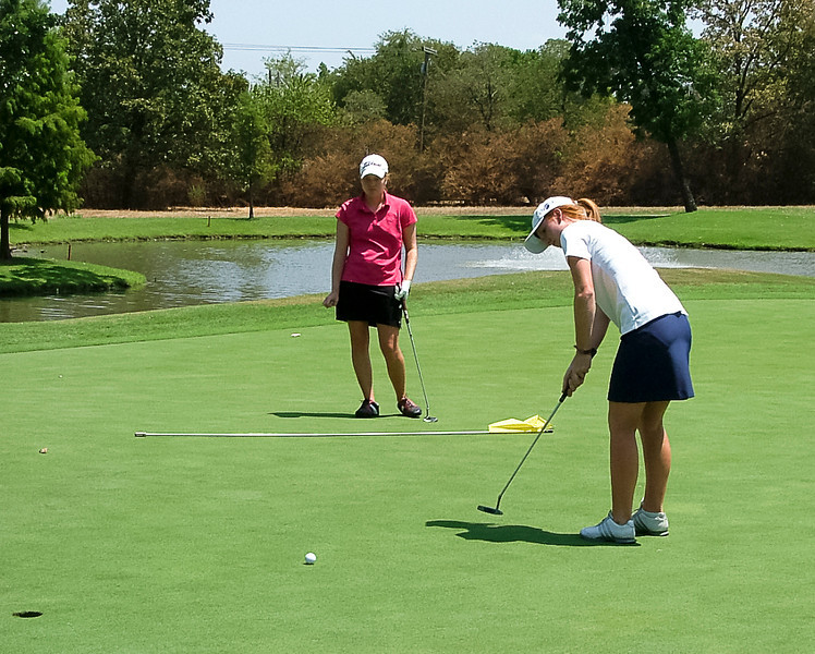 Morgan and McCall get a feel for the greens before getting started.