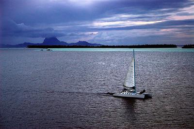 Sail boat fleeing a storm Bora Bora South Pacific French Polynesia