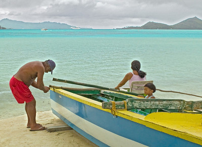 Man fixing boat w daughter Ta'Haa South Pacific; French Polynesia;