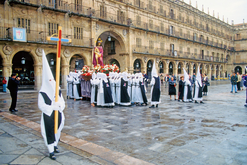 Holy Week in Salamanca's 'Plaza Mayor.' Masked people show selfless penance while carrying statues of Jesus and Mary.