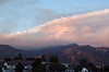 A subtropical cloud street moves over the pyrocumulus cloud from the fire burning behind Mt. Wilson as the sun sets. The interaction starts to build a lenticular cloud.