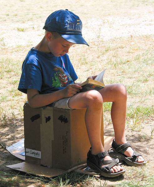 A child reading a book on an upturned box during our Quaker Meeting's Annual Book Fair held every second Saturday in July. (Westport Friends Meeting, 938 Main Road, Westport, MA, USA. You should come!)