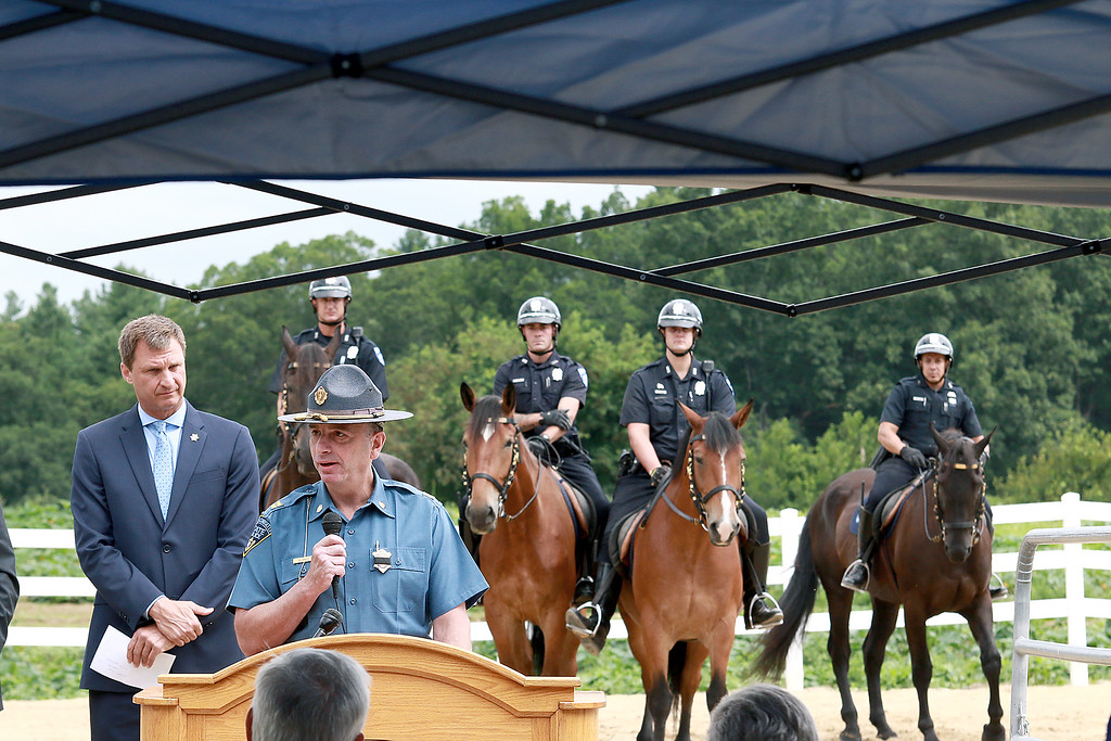 . Worcester County Sheriff Lew Evangelidis, on left, listens to Massachusetts State Police Captain Keith Blaney as he address the crowd during the ceremony. Just behind them, l-r, is Michael Dowd on Justice, Michael DiVirgilio on Myra, Eric Dowd on Major and David Rojas on Midnight. SENTINEL & ENTERPRISE/JOHN LOVE