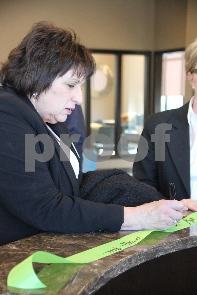 Pictured is Cheryl O'Hern signing the ribbon after the ribbon cutting ceremony, held on Thursday, February 18, 2016, for the Fort Dodge Family Credit Union in Fort Dodge.