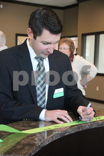 Pictured is Matt Johnson signing the ribbon after the ribbon cutting ceremony, held on Thursday, February 18, 2016, for the Fort Dodge Family Credit Union in Fort Dodge