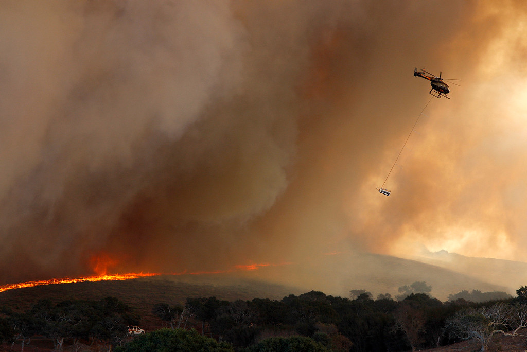. A helicopter uses a heli-torch to ignite the vegetation at the site of the Fort Ord prescribed burn on Thursday, Oct. 5, 2017.  Unit B of 265 acres and Unit C of a 145 acres were successfully burned.  (Vern Fisher - Monterey Herald)