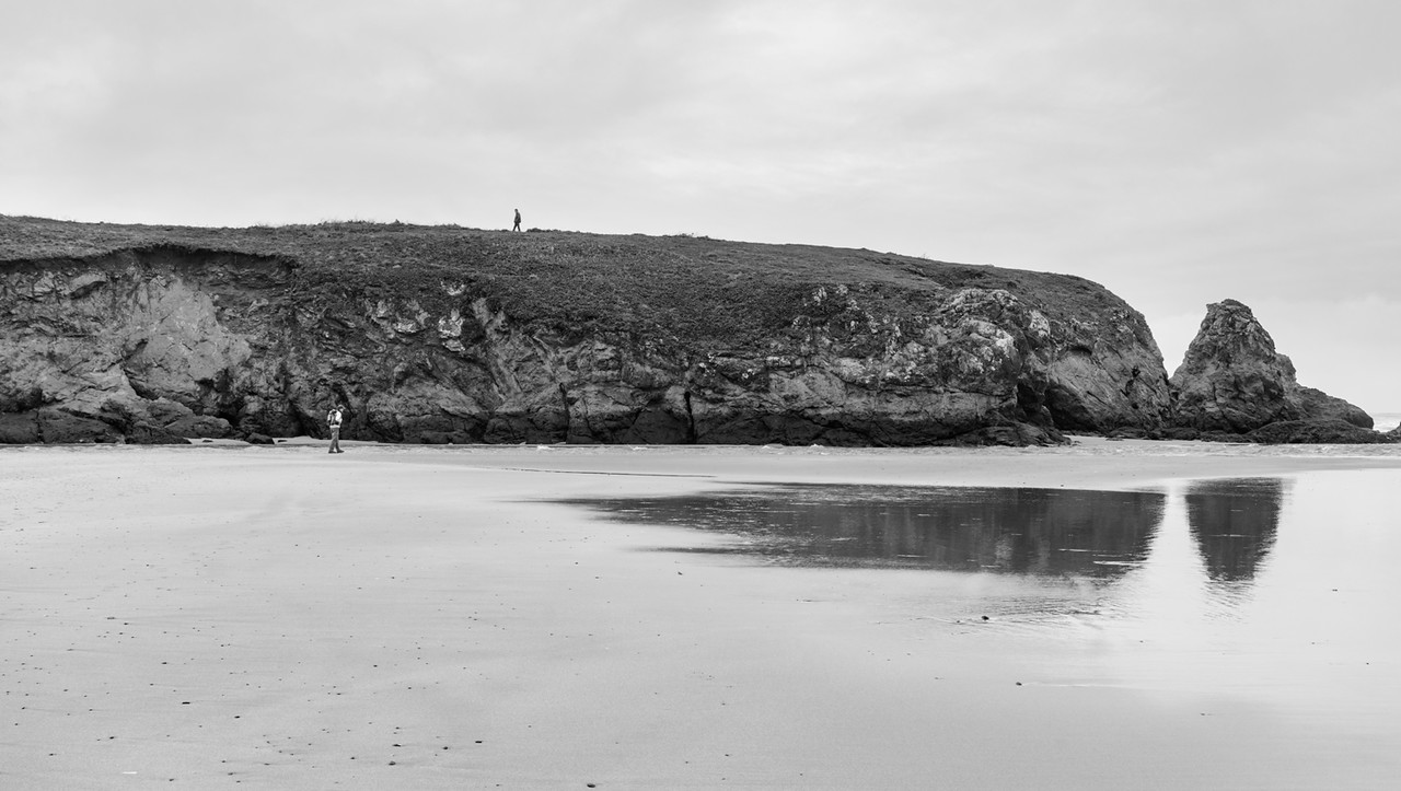 Guy on the beach.  Some other guy on the cliff top.