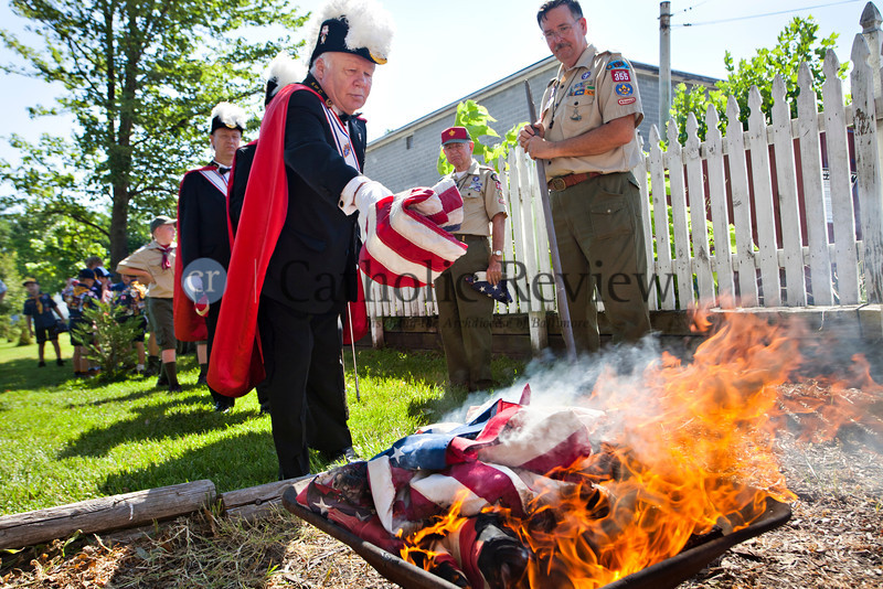 Pat Coyle, a members of the Knights of Columbus color guard, tosses an old flag into the fire during a Patriotic Ceremony for the Retirement of American Flags at St. Clement Mary Hofbauer, Rosedale une 22. TOM McCARTHY JR. | CR STAFF