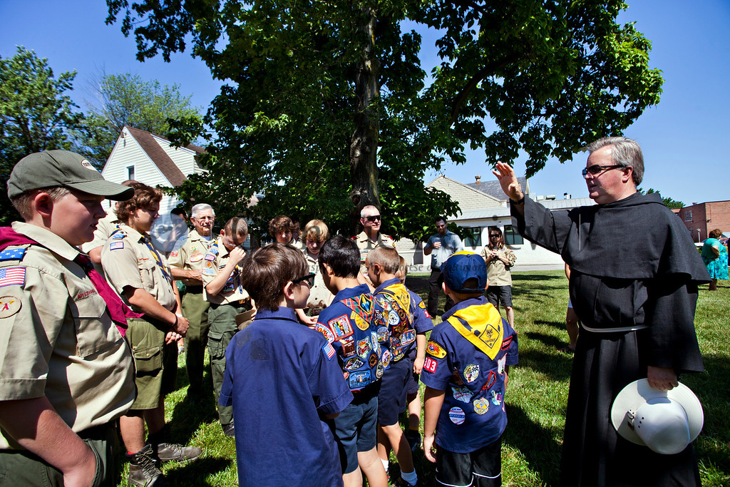 Members of Boy Scouts troops 355 and 303 recieve a blessing from Conventional Franciscan Father Donald Grzymski after a Patriotic Ceremony for the Retirement of American Flags at St. Clement Mary Hofbauer, Rosedale June 22. TOM McCARTHY JR. | CR STAFF