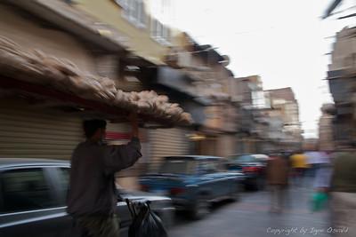 Kairo, Egipt (2011) - Kairski raznašalci kruha na kolesih kot bliski švigajo skozi gnečo Kaira.