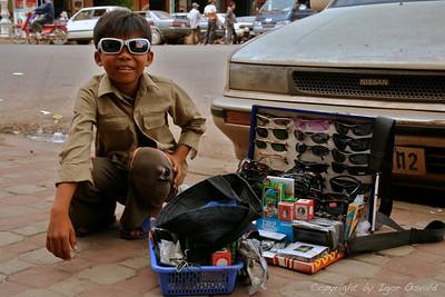 Phnom Penh, Kambodža (2006) - Prodajalec sončnih očal. Za učinkovit boj proti otroškemu delu, je potrebno najprej najti nadomestni prihodek za zaslužek, ki ga otroci prispevajo družini. Za učinkovit način se je pokazalo plačilo v obliki prehrambenih surovin (riž, olje), če otrok obiskuje šolo.