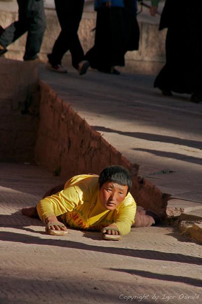 """Dege, Kham, Tibet/Kitajska (2010) - Prostracije. Roki z dlanmi skupaj na glavo, na vrat, na srce ter povaljka. In znova. Verni tako """"preplezajo"""" tudi na stotine kilometrov."""