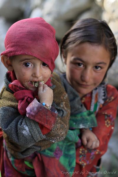 """Khandud, Wakhan, Afganistan (2011) - Ko se punčke igrajo, mimogrede s seboj nosijo oprtano še kakšno sestrico. Kot rugzak, ki pač mora biti tam. In čeprav se ta """"rugzak"""" med igro premetava na vse možne načine, le redko zajoka."""