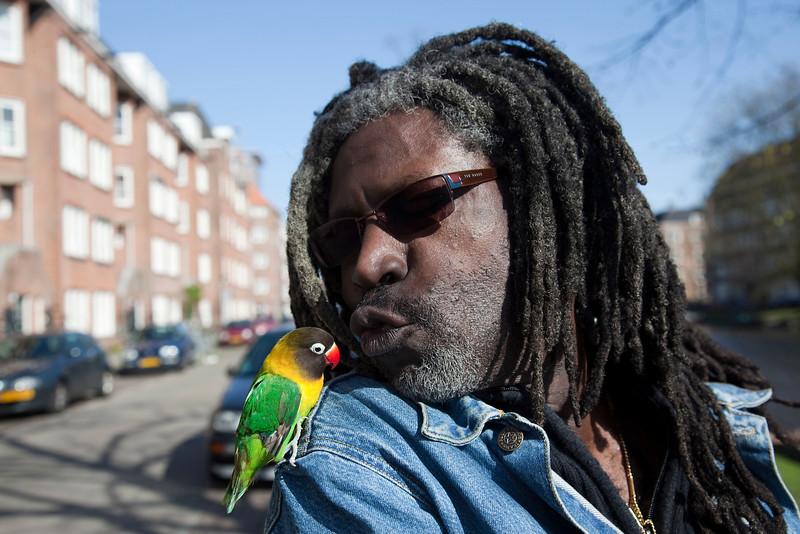 Nederland, Amsterdam, 15 april 2010, man met tropisch vogeltje,  jozef israelskade.<br /> foto: Katrien Mulder